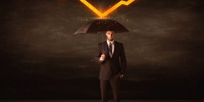 Businessman-standing-with-umbrella-keeping-orange-arrow-concept-on-background-1